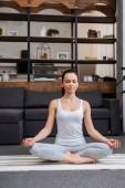 krásná mladá žena sedí v lotosu představují a meditoval doma v obývacím pokoji