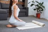 oříznutý pohled ženy sedí na fitness mat a cvičit hrdinu pozice doma