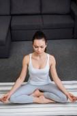 Fotografie mladá žena sedí v lotosu představují a meditovat s očima zavřené doma
