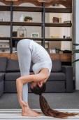 mladá žena cvičí, stojící předklon pozice doma v obývacím pokoji