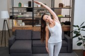 Fotografie beautiful young woman doing stretching exercise at home in living room