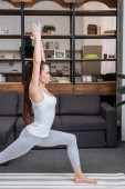 Fotografie focused young woman practicing warrior pose at home in living room