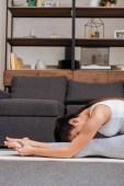 Fotografie žena cvičí sedící pozice přední fold na fitness mat doma v obývacím pokoji