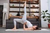 mladá žena cvičí salamba sarvangasana doma v obývacím pokoji