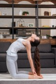 Photo woman practicing camel pose at home in living room