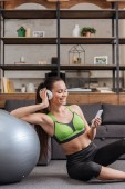 Photo smiling sportswoman in headphones sitting with fitness ball and using smartphone at home