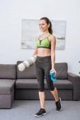 krásné sportovní sportovkyně s fitness mat a sportovní láhev doma