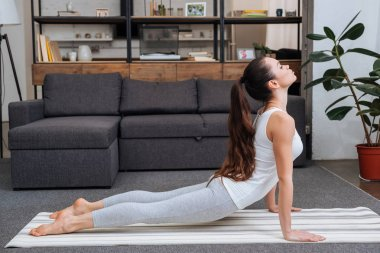 young woman practicing cobra pose in living room at home
