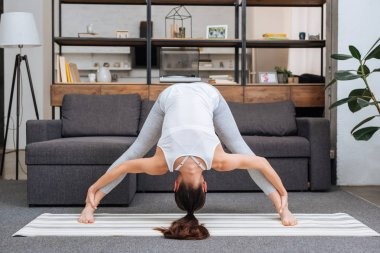 young woman practicing wide legged forward bend pose at home in living room