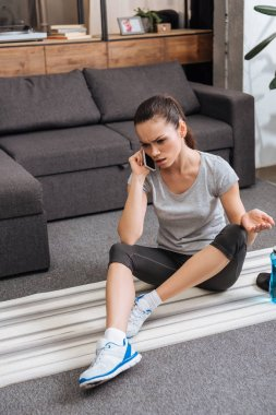 frustrated sportswoman sitting on fitness mat and talking on smartphone at home