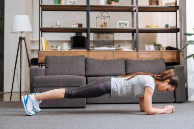 focused sportswoman doing plank exercise at home in living room