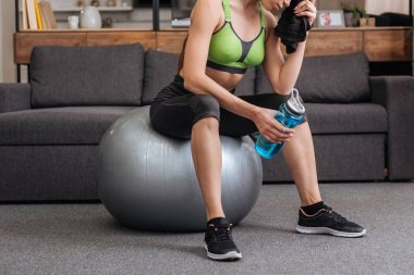 cropped view of tired sportswoman sitting on fitness ball with towel and sport bottle at home
