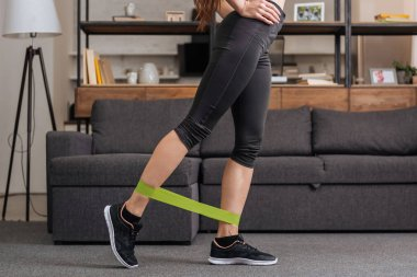 low section of sportswoman training with resistance band at home in living room