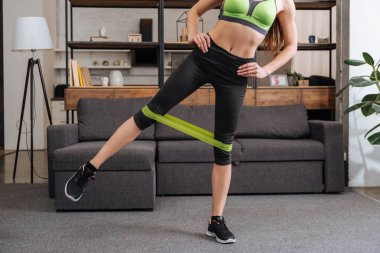 partial view of sportswoman training with resistance band at home in living room