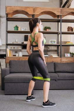 sportswoman working out with resistance band at home in living room