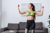 Fotografie smiling sportswoman training with dumbbells at home