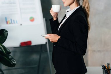 Cropped view of young businesswoman drinking coffee in office stock vector