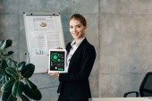 Pretty smiling businesswoman holding digital tablet with inphographics on screen