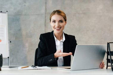 glad smiling businesswoman using laptop in office and pointing screen with hand