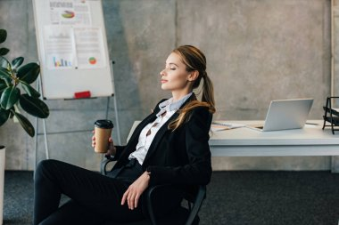 Young businesswoman seating on chair with closed eyes and holding paper cup of coffee