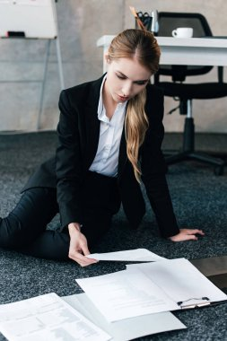 beautiful businesswoman sitting on floor near work-table and reading documents