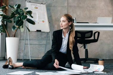 barefoot beautiful businesswoman sitting on floor near work-table and looking away