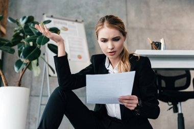 selective focus of beautiful businesswoman sitting on floor near work-table and holding document