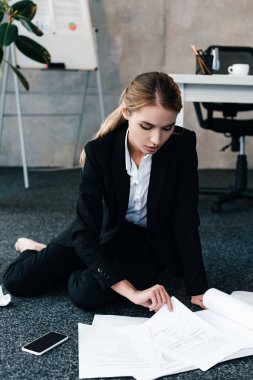 barefoot businesswoman sitting on floor near work-table and reading documents