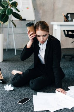 exhausted businesswoman sitting on floor near work-table with headache