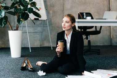 beautiful businesswoman sitting on floor near work-table and holding coffee