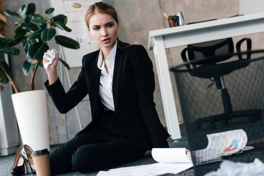 thoughtful businesswoman sitting on floor near work-table with coffee and documents