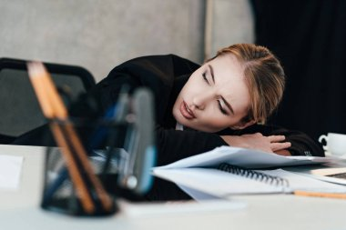 selective focus of beautiful businesswoman sleeping at work-table