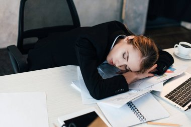 selective focus of tiredned businesswoman sleeping at work-table