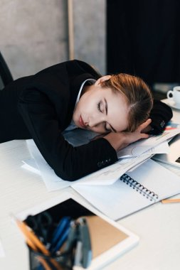 selective focus of exhausted businesswoman sleeping at work-table