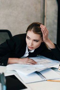 selective focus of tired businesswoman at work-table with documents
