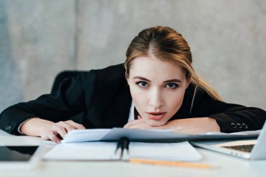 selective focus of businesswoman looking at camera and sitting at work-table with documents