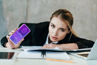 selective focus of businesswoman at work-table showing screen of smartphone with shopping