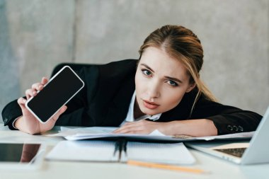 selective focus of businesswoman at work-table showing screen of smartphone