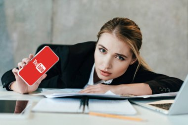 selective focus of businesswoman at work-table showing screen of smartphone with youtube website