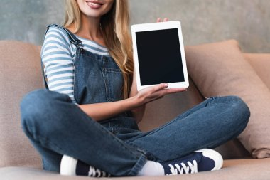 cropped view of girl sitting on sofa and showing screen of digital tablet