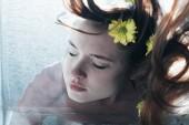 Fotografie zblízka krásná dívka pózování pod vodou se žlutými květy