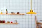 Fényképek fa polcok, üvegek és lámpa háttéren fehér csempe a konyhában