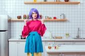 krásná žena v domácnosti s fialovými vlasy a barevné oblečení pózuje v kuchyni