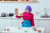 selective focus of housewife with purple hair and colorful clothes holding plate of pancakes in kitchen