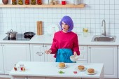 housewife with purple hair and colorful clothes cooking pancakes in kitchen