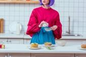 částečný pohled hospodyně s fialovými vlasy a barevné oblečení připravují palačinky v kuchyni