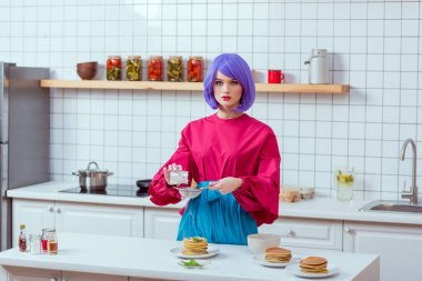housewife with purple hair and colorful clothes looking at camera while preparing pancakes in kitchen