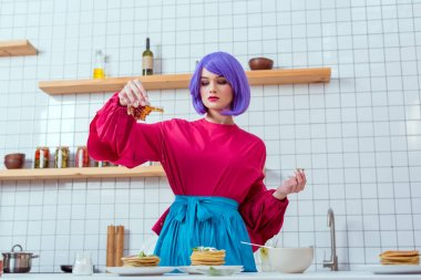 Focused housewife with purple hair and colorful clothes pouring syrup on pancakes in kitchen stock vector