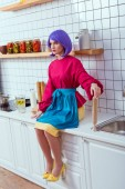 selective focus of housewife with purple hair sitting on kitchen counter with rolling pin