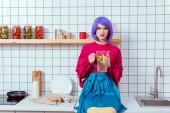 Hospodyně s fialovými vlasy a barevné oblečení sedí na kuchyňské lince a držení sklenice limonády
